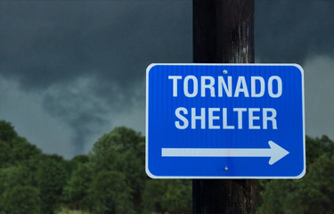 Tornado shelter sign with a small funnel cloud on background - concept for immediate danger in severe weather and seeking for shelter