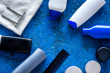 Men's cosmetics for hair care and shaving. Shampoo, gel, razor, wax on blue background top view copyspace