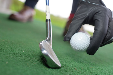 person holding golf ball close-up