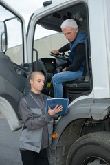 manager talking to truck driver in a warehouse