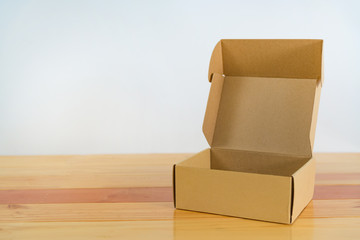 Empty brown cardboard box on wooden table with copy space.