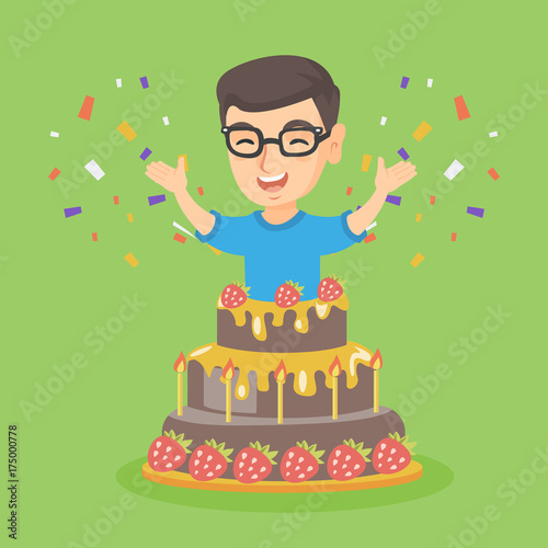 Little caucasian boy jumping out of a large cake Smiling boy
