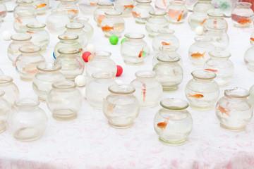 Pesciolini rossi che nuotano nell'acqua in bocce di vetro sulla bancarella in una fiera