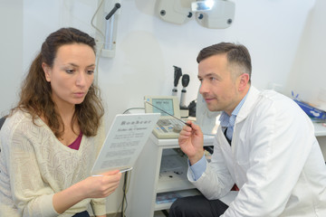 ophthalmologist asking patient to read page