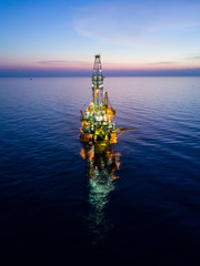 Wall Mural - Aerial View of Tender Drilling Oil Rig (Barge Oil Rig) in The Middle of The Ocean at Sunrise Time