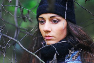 Beautiful pensive woman with brown eyes wearing a scarf and a hat in the Park among the bare branches of trees, closeup