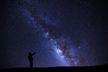 A Man is standing pointing on a bright star with milky way galaxy and space dust in the universe