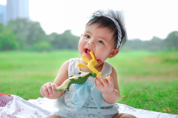 Asian Adorable baby girl playing with toy in park. Beautiful smiling cute baby