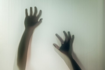 Halloween hands behind transparent glass background as silhouette
