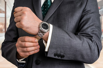 Businessman in black suit checking time from watch