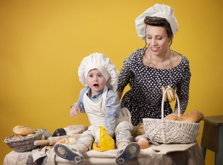Mother and son in the costume of the chefs playing with flour on yellow isolated background