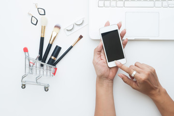 Beauty items, Brushes set in shopping cart with woman hand holding mobile phone, Top view shopping online concept