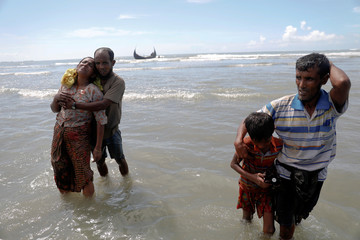 Exhausted Rohingya refugees arrive by a wooden boat from Myanmar to Shah Porir Dwip