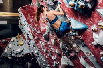 Female climber. Extreme indoor climbing.