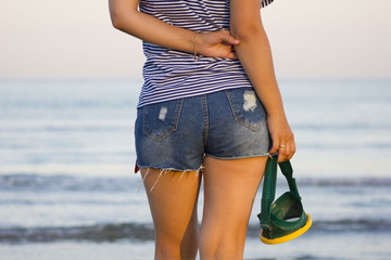 Девушка стоит на пляже в джинсовых шортах с маской для подводного плавания