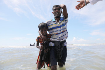 People are helped to the shore after getting off the wooden boat bringing Rohingya refugees from Myanmar to the shore of Shah Porir Dwip