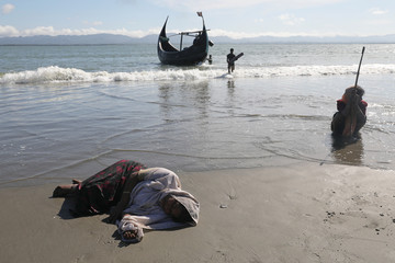 Women collapse from exhaustion as Rohingya refugees arrive by a wooden boat from Myanmar to the shore of Shah Porir Dwip