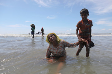 A woman is helped by a child as Rohingya refugees arrive by a wooden boat from Myanmar to the shore of Shah Porir Dwip