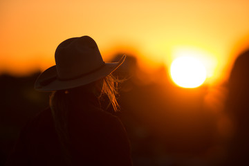 cowgirl with hat in the sunset