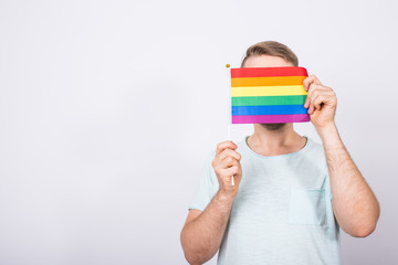 Male standing with hand holding the rainbow flag. Concept of sexual minority and LGBT