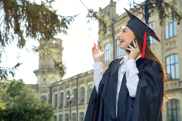 Woman on her graduation day. Use smart phone. University, education, digital technology, mobile communication and happy people - concept.