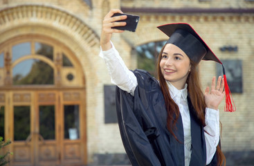Woman on her graduation day. Use a smartphone while doing a self portrait photo. University, education, digital technology, mobile communication and happy woman - concept.