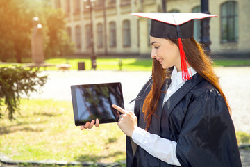 Woman on her graduation day. Use tablet pc. University, education and happy people - concept.