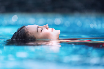 Young asian woman relaxing in swimming pool at spa resort.