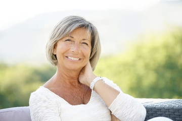 Portrait of cheerful senior woman relaxing in outdoors sofa