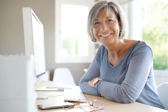 Portrait of mature businesswoman working on desktop