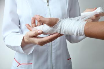 A nurse bandages a patient's hand