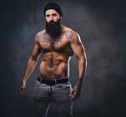 Shirtless muscular, bearded male holds dumbbell.