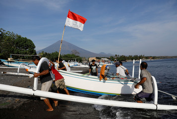 An Indonesian flag is seen on a boat as fisherman carry it on to the beach with Mount Agung, a volcano on the highest alert level located some 15 km away, in the background in Amed, on the resort island of Bali