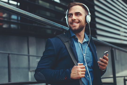 Handsome young man listen to music via smartphone and headphones on the street