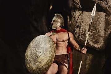 Muscular confident man in helmet and armor of ancient Roman warrior holding spear and shield looking confidently away on nature. Spartan.