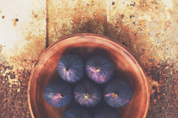 Ripe figs in clay bowl on rusted metal background