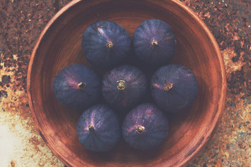 Ripe purple figs on clay plate