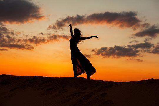 Female figure against the backdrop of the setting sun.