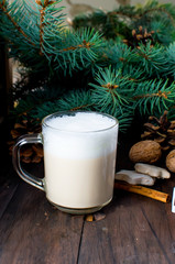 Cup of hot coffee latte, cinnamon, cookies and fir branches.