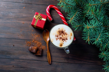 Cup of hot coffee latte, cinnamon, cookies and fir branches and gift