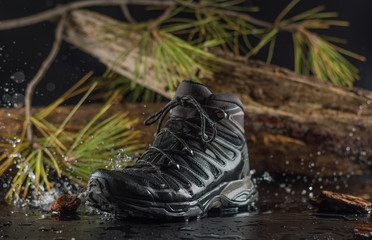 Black hiking boots, wet by a puddle of water