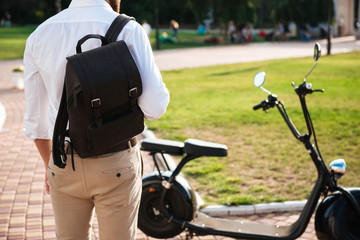 Cropped back view of man with backpack standing near motorbike