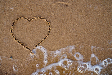 Top view of heart drawn on sand beach with the wave of sea. Beach background