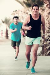 Two sportsmen jogging in park