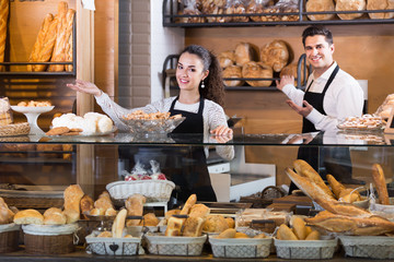 Fotobehang Bakkerij Cheerful couple selling pastry and loaves