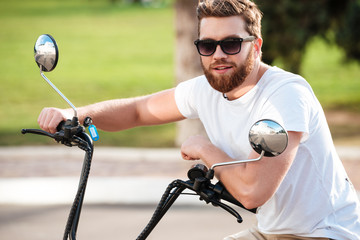 Cheerful bearded man in sunglasses sitting on modern motorbike