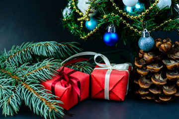 Pine cone and gifts wrapped in a red paper with white ribbon under decorated Christmas tree. Concept of Merry Christmas and New Year