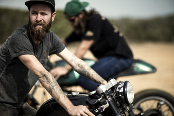 Side view of bearded man with tattoos on his arm sitting on cafe racer motorcycle on a dusty dirt road.