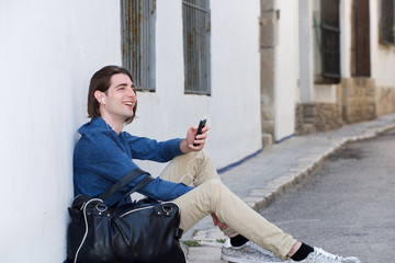 Laughing man on city street with smart phone and bag