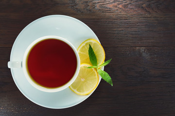 White cup of tea with cinnamon sticks, lemon, mint leaves and tea strainer on wooden rustic table.